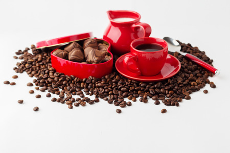 Cup of coffee, milk and a box (heart-shaped) with chocolates on the coffee beans. Isolated on white background.