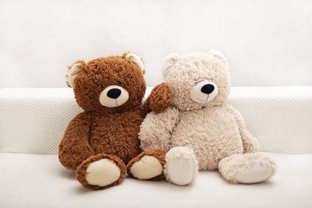 Juguetes para niños: osos de color marrón y beige están sentados en el sofá. Enfoque selectivo.