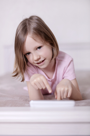 Little girl in pink pajamas on the bed is looking at a smartphone. Selective focus.