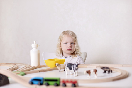 Little cute baby boy (3 years old) drinks milk with cookies and plays in the wooden station train set on the table. Selective focus.