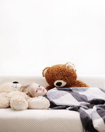 Small baby (a boy of three years old) is lying on the sofa under the rug with a teddy bear toys. Selective focus.