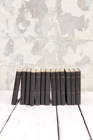 Stack of old ancient shabby books on a white wooden