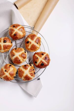 Buns marked with a cross and containing dried fruit, traditionally eaten during Lent. Selective focus.