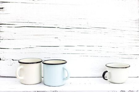 Enameled mugs in retro style on an old wooden background. Selective focus.