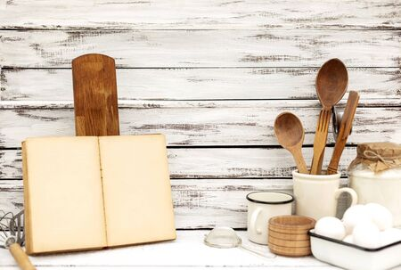 Vintage old baking kitchenware and recipe book on white wooden Standard-Bild