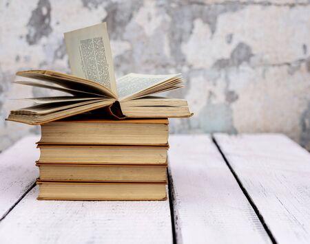 Pila de viejos libros antiguos en mal estado en una madera blanca