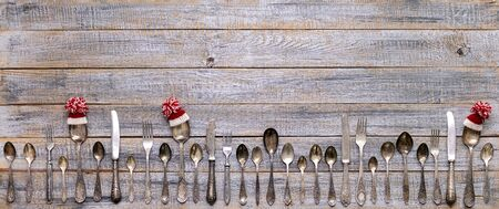 Merry Christmas! Vintage cutlery in santa claus hats on old wooden background. Background with copy space.