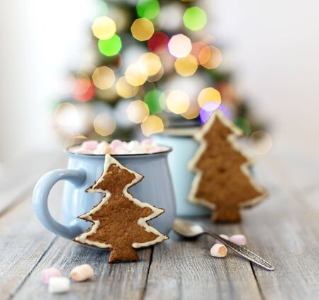 Merry Christmas! Christmas tree-shaped gingerbread cookie near cups of cocoa and marshmallows. Beautiful blurred christmas tree background with luminous garland. Selective focus.