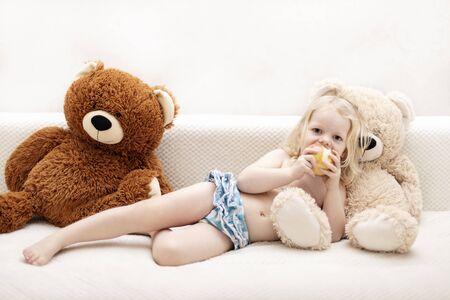 Kleines Baby (ein Junge von drei Jahren) liegt auf dem Sofa unter dem Teppich mit einem Teddybär-Spielzeug. Selektiver Fokus.