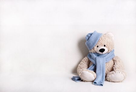 Children's toy teddy bear is sitting on a white sofa in a knitted scarf and hat in blue. Selective focus. 版權商用圖片