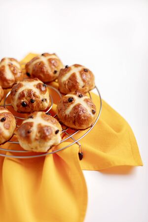 Buns marked with a cross and containing dried fruit, traditionally eaten during Lent.