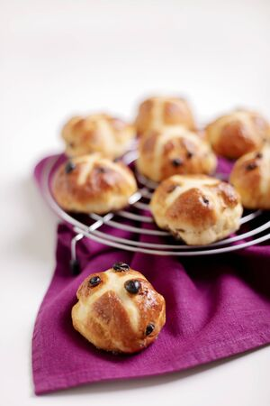 Cross-buns containing dried fruits are traditionally eaten during Lent before Easter. Selective focus.