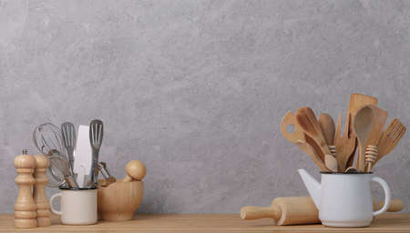 Kitchen tools, utensils and kitchenware on the table on a gray concrete background. Selective focus.