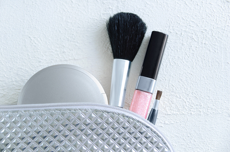 Silvery cosmetic bag with a powder brush for powder lip gloss and makeup brush on a white rough background Stock fotó