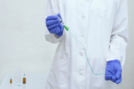 A urologist in a white lab coat and blue sterile gloves holds a catheter in his hands