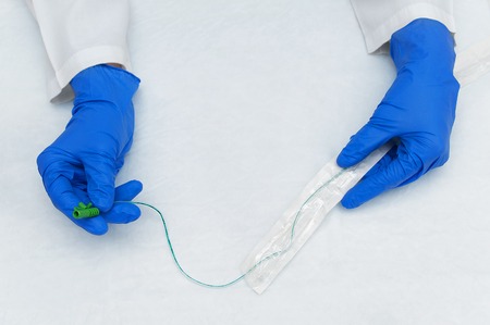 The hands of a urologist in a white lab coat and blue sterile gloves take out a catheter from a sterile package