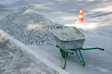 An empty construction cart on the sidewalk. It stands at a pile of rubble. Imagens