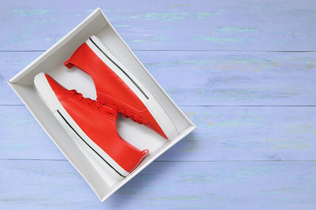 Red sneakers in a box. On a blue wooden background. Stock fotó