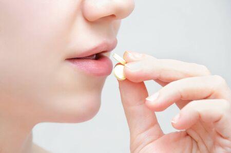 Fille avec une pilule à la main, bouche ouverte. Fermer.