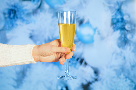 Wine glass with champagne in hand against the background of the Christmas tree. Close-up