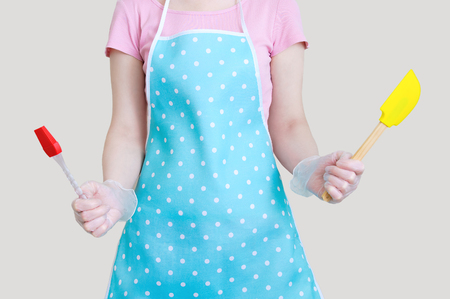 Silicone spatula and brush for cooking in the hands of the girl. Close-up. Gray background