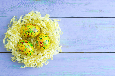 Colored easter eggs in yellow paper shavings. On blue wooden background.