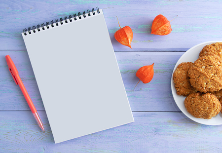 Notepad, pen, dried flowers and cookies in the plate. On wooden blue background.