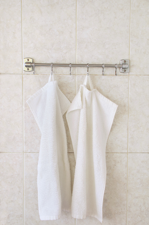 Two white terry towels on a hanger on the background of a wall of ceramic tiles.