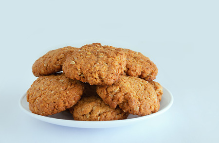 Oatmeal cookies with cereals and seeds on a white plate. White background. Close-up.