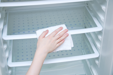 Hand caucasian girl with a white rag washes the fridge. Close-up. Stock fotó
