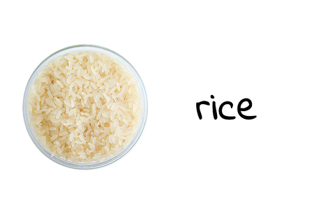 Rice grits in a glass bowl. View from above. White isolate