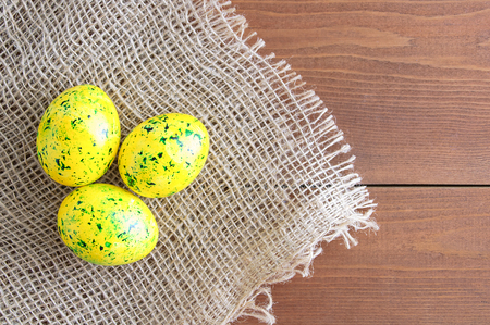 Easter eggs of yellow color with green splashes. On linen fabric brown. Wooden brown background.