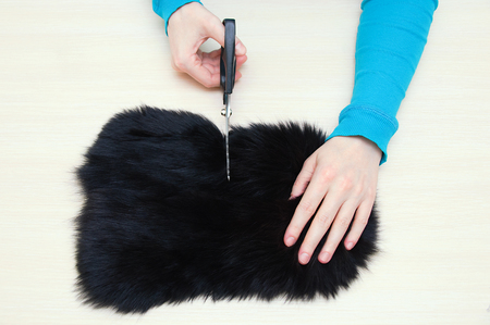 Caucasian girl cuts fur skin with black scissors on the table.View from above. Фото со стока - 120640269