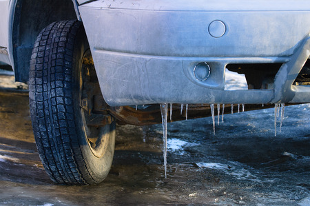 Old dirty car. Ice icicles on the bumper. Close-up. Stock Photo