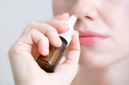 Spray nasal. Belle jeune femme. Fermer. Visage avec des gouttes nasales. Gros plan sur une femme pulvérisant un spray nasal médical dans son nez. Rhume et grippe, concept de soins de santé.