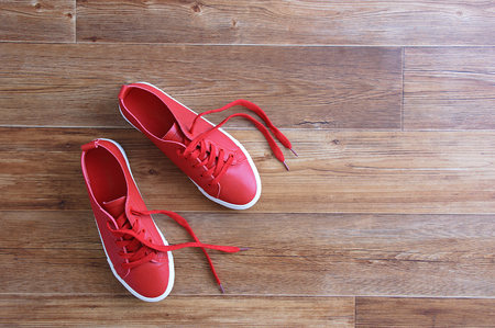 Red sneakers stand on a brown wooden floor. View from above.