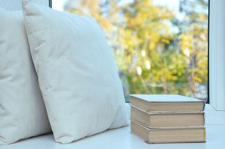 In the summer a white pillow and books stand on the windowsill by the window. Stock Photo