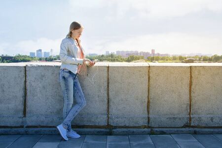 Girl in headphones with a smartphone in hand. Standing on the waterfront. On the background of the urban landscape.