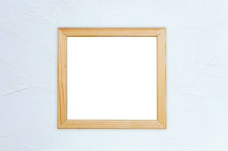 Wooden photo frame on a white wall. Place for text