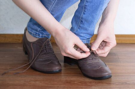 Caucasian girl tying shoelaces on brown shoes. Close-up. 免版税图像