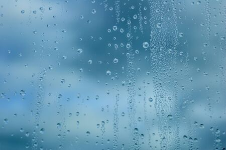 Drops of water on glass against the background of the sky of dark thunderclouds. Close-up. Imagens
