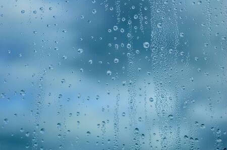 Gocce d'acqua su vetro sullo sfondo del cielo di nuvole temporalesche scure. Avvicinamento. Archivio Fotografico