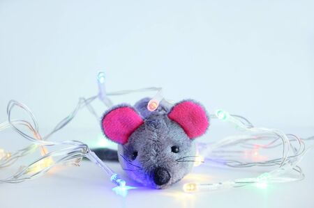 Gray soft toy mouse with Christmas garland on a white background close-up.