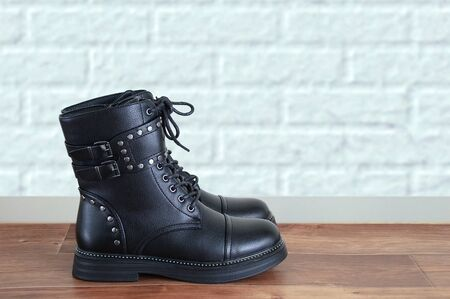 Close-up of black biker boots with metal fittings on a background of a brick white wall.