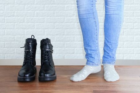 Legs of a girl in blue jeans and socks next to a pair of black boots. Against the background of a white brick wall.