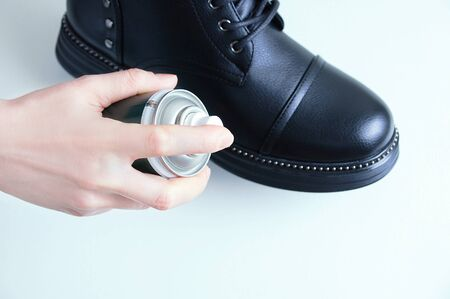 Leather shoe care. Black shoe and water repellent spray for shoes in the hands of a Caucasian woman. View from above. Reklamní fotografie