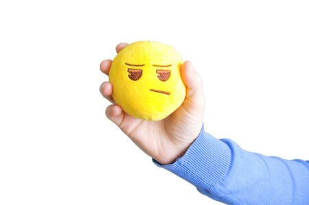 Yellow round soft toy sad emoticon in the hand of a caucasian girl. White isolate. Reklamní fotografie
