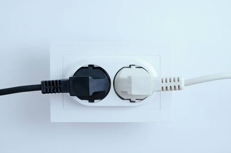 Electrical plugs from electrical appliances white and black are included in the socket on a white background. Close-up.