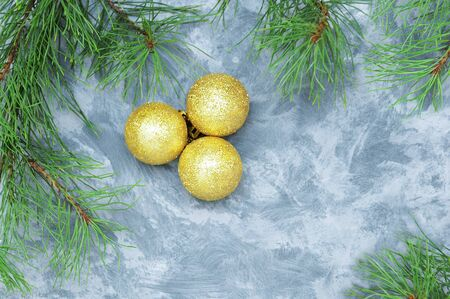 Christmas golden balls and christmas tree branches on a gray background. View from above.