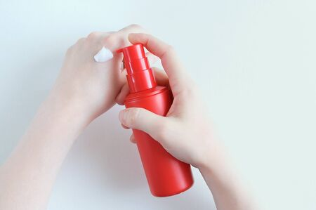 Red plastic bottle with hand cream in the hands of a caucasian girl. View from above. Reklamní fotografie